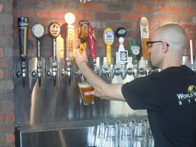 Ty Young, a bartender at World of Beer in Tucson, Arizona, pours a pint of Mudshark Full Moon Lunacy for a customer. The tap room has a selection of more than 600 craft beers.